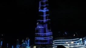 Tourists watch skyscraper illumination show in night Dubai. Tourist crowd silhouettes watch changing world famous skyscraper light illumination show in Dubai stock video