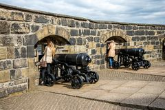 Tourists watch thru the cannon slots at Half Moon Battery in Edinburgh Castle. Tourists watch thru the gun-slots at Half Moon Battery in Edinburgh Castle Royalty Free Stock Image