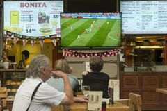 Tourists watching football game Stock Photo
