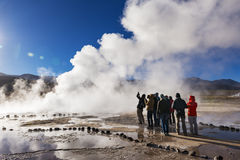 Tourists watching a geyser in the Geysers del Tatio field in the Atacama Desert, Northern Chile. Geysers del Tatio, Chile - November 24, 2013: Tourists watching Stock Images