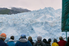 Tourists watching glacier in Alaska, USA. Group of tourists watching melting glacier from tour boat at Prince William Sound, Alaska, USA Royalty Free Stock Photo