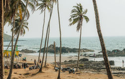 Tourists watching the ocean beach with palm trees around and some outdoor cafe. GOA, INDIA - MARCH 2: Tourists watching the ocean beach with palm trees around Royalty Free Stock Photos