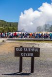 Tourists watching the Old Faithful erupting in Yellowstone Natio Royalty Free Stock Image