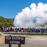 Tourists watching the Old Faithful erupting in Yellowstone Natio Stock Photo