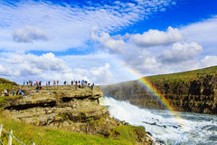 Tourists watching rainbow on waterfall in Iceland. Tourists watching a steamy Gullfoss waterfall with rainbow in Iceland Stock Photo