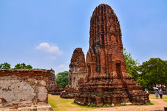 Tourists are watching the ruins of the pagoda and the Buddha statue in Wat Mahathat, Stock Photography