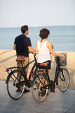 Tourists watching at the sea. Tourists with rented bikes walking Stock Images