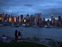 Tourists watching the silhouette of Lower Manhattan at night sky background Stock Images