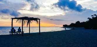 Tourists watching sunrise on Atlantic ocean island resort. Couple watching sunrise on ocean beach resort Stock Photo
