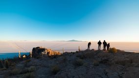 Tourists watching sunrise at Uyuni Salt Flat, travel destination in Bolivia. Wide angle shot from the summit of the Incahuasi Isla. Nd Royalty Free Stock Photo