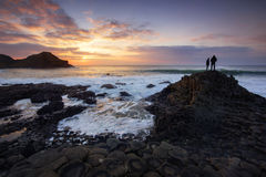 Tourists watching a sunset at the Giant's Causeway Royalty Free Stock Image