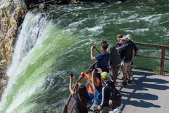YELLOWSTONE NATIONAL PARK, WYOMING, USA - JULY 17, 2017: Tourists watching and taking pictures of Lower Yellowstone Falls. Grand C. Tourists watching and taking Royalty Free Stock Images