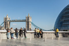 Tourists watching Tower bridge. LONDON, UK - MARCH 25, 2016: Tourists watch Tower bridge on a sunny Spring day Royalty Free Stock Image