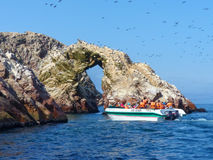 Tourists watching wildlife in Ballestas Islands Reserve in Peru. Ballestas islands are an important sanctuary for marine fauna Royalty Free Stock Photography