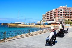 Tourists on waterfront benches, Marsalforn. Tourists sitting on benches along the promenade with views towards beach and harbour, Marsalforn, Gozo, Malta Stock Images