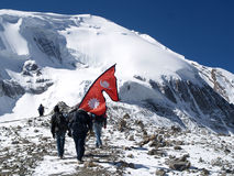 Tourists waving Nepali Flag. Nepali tourists waving the flag of Nepal in the mountain in Thorong La Pass.Thorong La is the highest point on the Annapurna Circuit Stock Photo