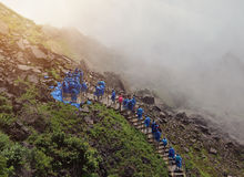 Tourists Wearing Raincoats Walking up Niagara Falls. Tourists are walking up a stairway to Niagara Falls with wet water mist and blue raincoats on for a travel Royalty Free Stock Images