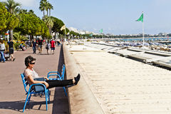 Tourists and the weather along the Boulevard de la Croisette in Royalty Free Stock Photos