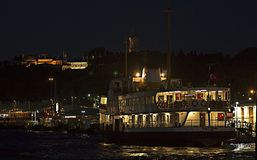 A public ferry called `Vapur` at Eminonu Port under the Topkapi Palace of the Ottoman Empire by night. royalty free stock photos