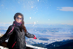 Tourists woman  enjoying the winter mountain view and throwing snow in a ski resort .Bulgaria,Borovets Royalty Free Stock Photography