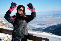 Tourists woman  enjoying the winter mountain view and waving hello. Young  woman smiling  in a winter mountain .beautiful Blue sky Royalty Free Stock Photos
