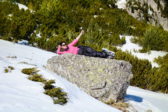 Tourists woman  lying on a stone and enjoying the winter sun Royalty Free Stock Image