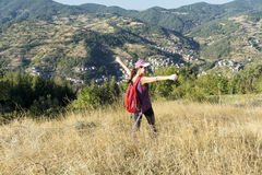 Tourists woman spreading arms in the mountain royalty free stock image