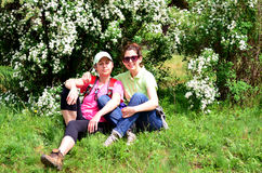 Tourists women sitting and hugging under a blooming white bush.Family portrait Royalty Free Stock Photo