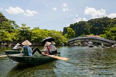 Tourists in wooden boats to travel Tam Coc. Tourists in boats to travel along Ngo Dong River at Tam Coc, Ninh Binh Province, Vietnam. Vietnamese Rowers using Royalty Free Stock Photo