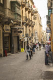 Tourists and workers in side street at Valletta on Malta. Tourists and workers in architecturally interesting side street at Valletta on Malta Royalty Free Stock Image