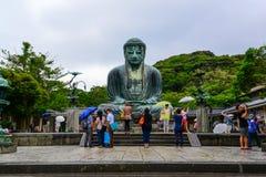 Tourists worshiping beautiful and famous giant bronze Buddha Sta Stock Image