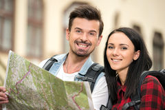 Tourists. Young tourists with touristic map and tablet walking in the town. Looking at the camera Stock Images