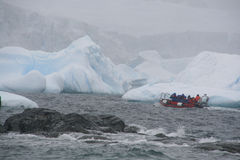 Tourists in zodiac offshore among icebergs