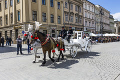 Touristsa enjoy a carriage ride at the Market Square in Krakow Royalty Free Stock Images