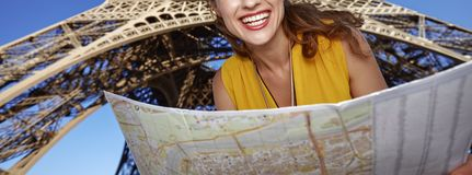 Closeup on happy woman with map against Eiffel tower, Paris. Touristy, without doubt, but yet so fun. Closeup on happy young woman with map against Eiffel tower Royalty Free Stock Images
