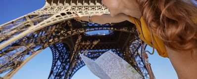 Woman holding map and pointing on Eiffel tower, Paris. Touristy, without doubt, but yet so fun. Closeup on young woman holding map and pointing on Eiffel tower Royalty Free Stock Photo