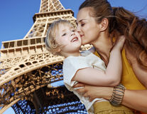 Happy mother and child tourists kissing against Eiffel tower Royalty Free Stock Images
