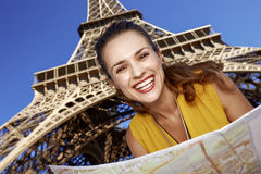 Happy woman with map against Eiffel tower, Paris. Touristy, without doubt, but yet so fun. happy young woman with map against Eiffel tower in Paris, France Stock Photography