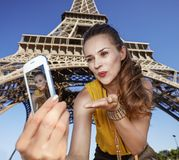 Woman taking selfie and blowing air kiss near Eiffel tower. Touristy, without doubt, but yet so fun. happy young woman taking selfie with smartphone and blowing Stock Image