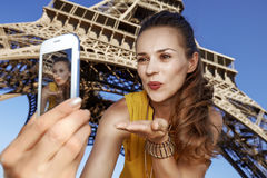 Woman taking selfie and blowing air kiss near Eiffel tower. Touristy, without doubt, but yet so fun. happy young woman taking selfie with smartphone and blowing Royalty Free Stock Photography