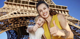 Happy mother and daughter travellers showing thumbs up in Paris Stock Photography