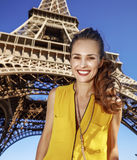 Portrait of happy woman against Eiffel tower in Paris, France. Touristy, without doubt, but yet so fun. Portrait of happy young woman against Eiffel tower in Stock Photo