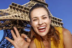 Woman showing ok gesture in front of Eiffel tower, Paris Stock Photos