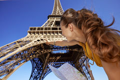 Woman holding map and pointing on Eiffel tower, Paris. Touristy, without doubt, but yet so fun. Seen from behind young woman holding map and pointing on Eiffel Royalty Free Stock Image