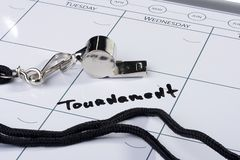 Tournament Date. A silver whistle laying next to the word Tournament drawn on a calendar Stock Images