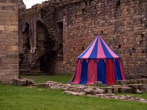 Tournament. Medieval castle ruins with tournament tent in bright colours, Northumberland, re enactment Stock Image