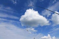 Tournant, ligne de pêche et platine sur un nuage blanc Photographie stock libre de droits