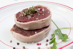 Tournedos: a small round thick cut from a fillet of beef in a white plate background Stock Photo