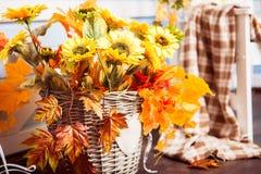 Tournesols dans le panier en osier décoré des feuilles jaunes Images stock