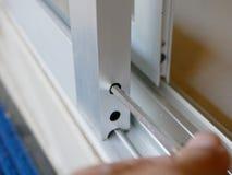 Tournevis dans la main d'un homme ajustant les rouleaux de porte en verre de glissement image stock